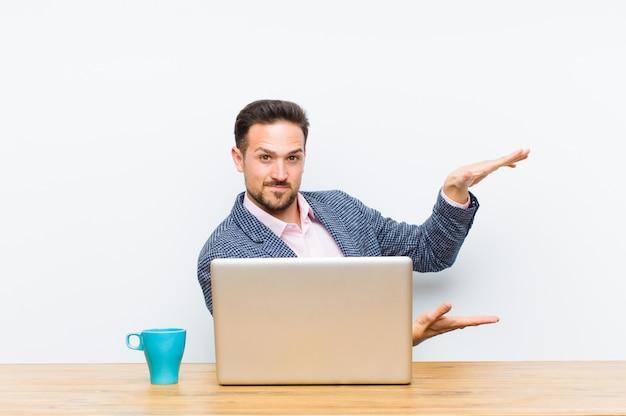 Jeune bel homme d'affaires tenant un objet avec les deux mains sur l'espace de copie, montrant, offrant ou annonçant un objet