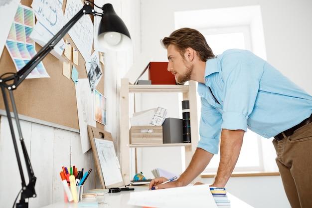 Jeune bel homme d'affaires travaillant debout à table et regardant à travers les papiers épinglés au tableau de liège.