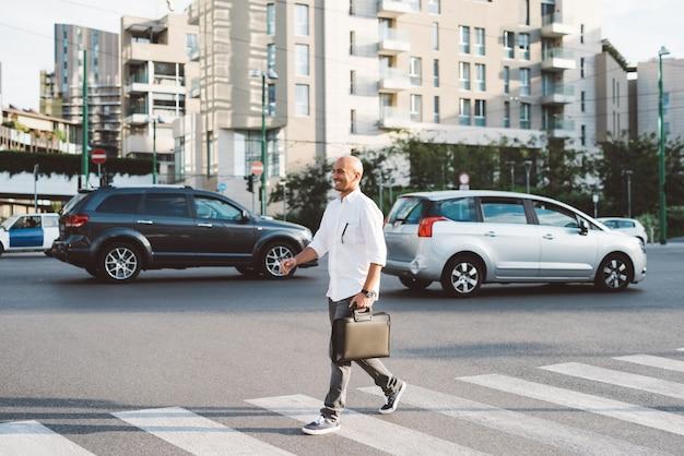 Jeune bel homme d'affaires traversant la rue