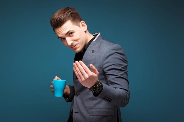 Jeune bel homme d'affaires en veste grise et chemise noire tenir tasse bleue