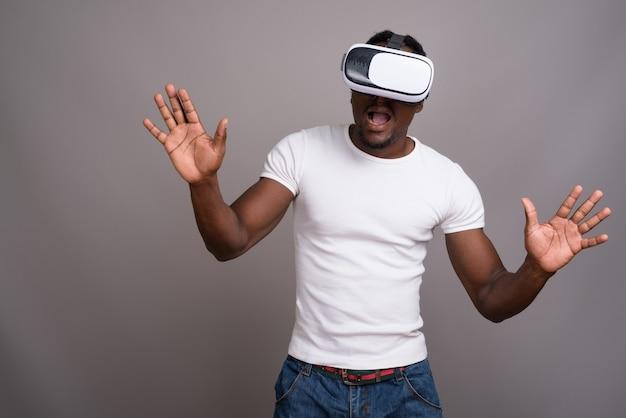 Jeune bel homme africain à l'aide d'un casque de réalité virtuelle contre
