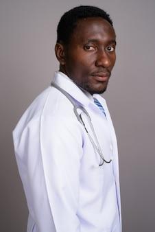 Jeune bel homme africain médecin sur fond gris