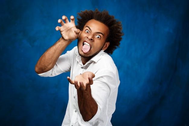 Jeune bel homme africain montrant la langue, tromper sur le mur bleu.