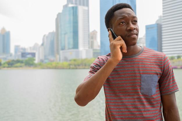 Jeune bel homme africain parlant au téléphone dans le parc