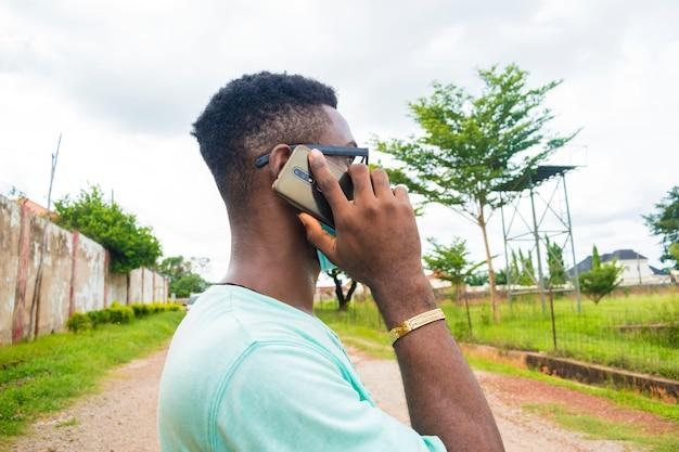 Jeune bel homme africain portant un masque facial faisant des appels avec son téléphone portable.