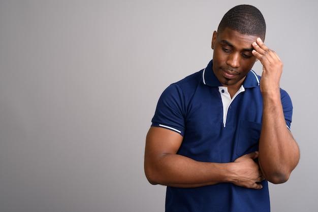 Jeune bel homme africain portant un polo bleu sur fond gris