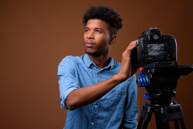 Jeune bel homme africain vlog avec appareil photo reflex numérique en studio