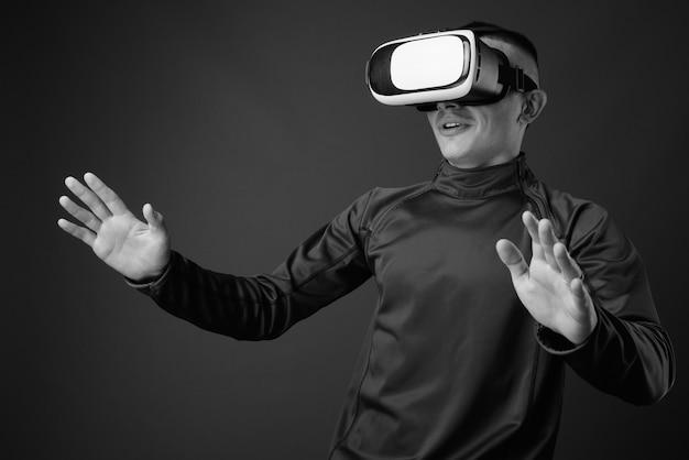 Jeune bel homme à l'aide d'un casque de réalité virtuelle contre un mur gris. noir et blanc