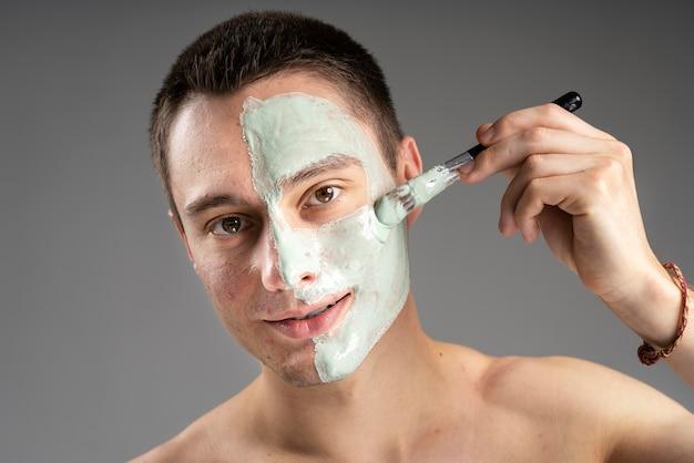 Jeune bel homme à l'aide d'un masque pour l'acné