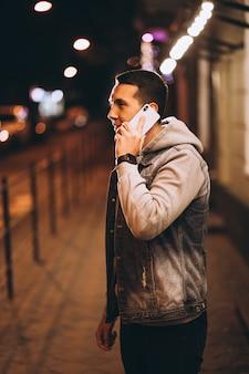 Jeune bel homme à l'aide de téléphone la nuit dans la rue