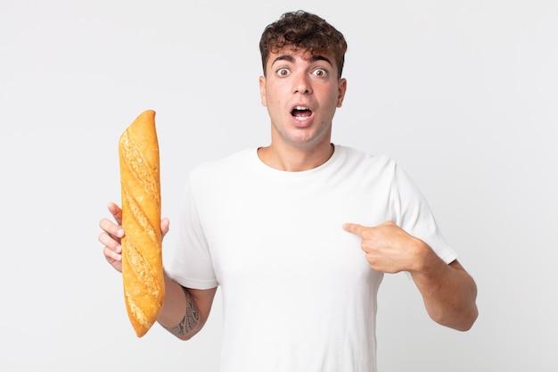 Jeune bel homme à l'air choqué et surpris avec la bouche grande ouverte, pointant vers lui-même et tenant une baguette de pain