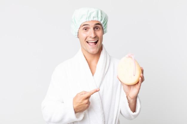 Jeune bel homme à l'air excité et surpris pointant sur le côté avec un peignoir, un bonnet de douche et une éponge