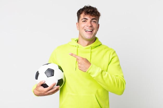 Jeune bel homme à l'air excité et surpris pointant sur le côté et tenant un ballon de football