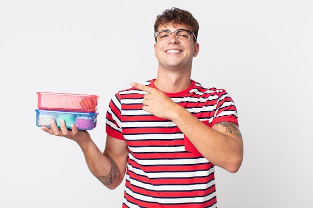 Jeune bel homme à l'air excité et surpris pointant sur le côté et tenant une boîte à lunch