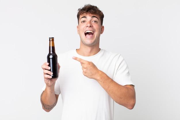 Jeune bel homme à l'air excité et surpris pointant sur le côté et tenant une bouteille de bière