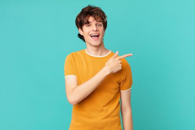 Jeune bel homme à l'air excité et surpris en pointant sur le côté