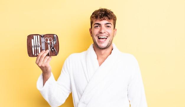 Jeune bel homme à l'air heureux et agréablement surpris. concept de cas d'outils d'ongles