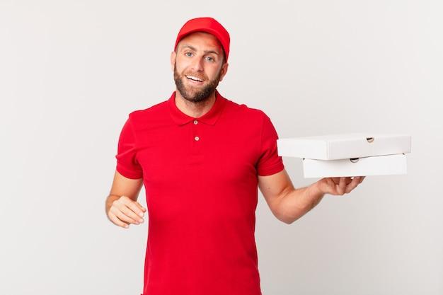 Jeune bel homme à l'air heureux et agréablement surpris. concept de livraison de pizza