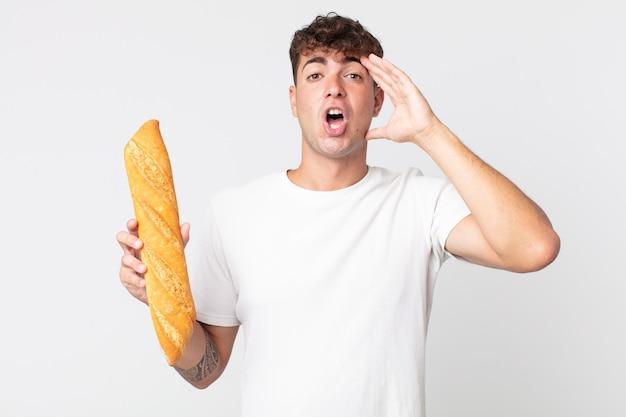 Jeune bel homme à l'air heureux, étonné et surpris et tenant une baguette de pain