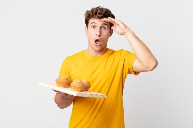 Jeune bel homme à l'air heureux, étonné et surpris tenant un plateau à muffins