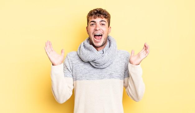 Jeune bel homme à l'air heureux et excité, choqué par une surprise inattendue avec les deux mains ouvertes à côté du visage