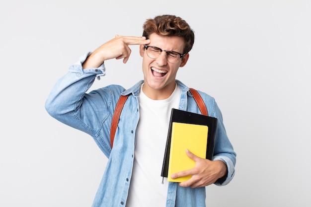 Jeune bel homme à l'air malheureux et stressé, geste de suicide faisant signe d'arme à feu. concept d'étudiant universitaire