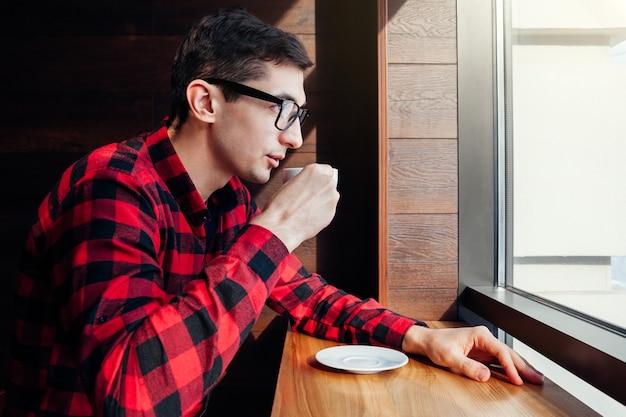 Le jeune bel homme apprécie le café dans le café devant la fenêtre