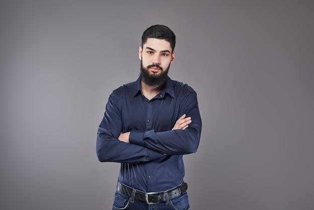 Jeune bel homme appuyé contre un mur gris avec les bras croisés. un jeune homme sérieux avec une barbe regarde la caméra. copiez l'espace.