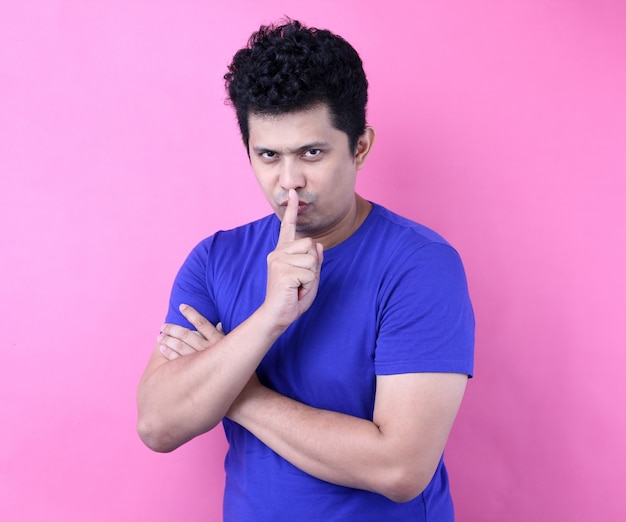 Jeune bel homme asiatique demandant de se taire avec le doigt sur les lèvres. silence et concept secret.