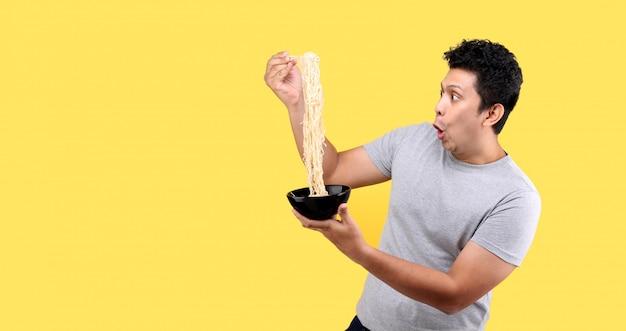 Jeune bel homme asiatique à la mode mangeant de délicieuses nouilles instantanées chaudes et épicées à l'aide de baguettes et d'un bol