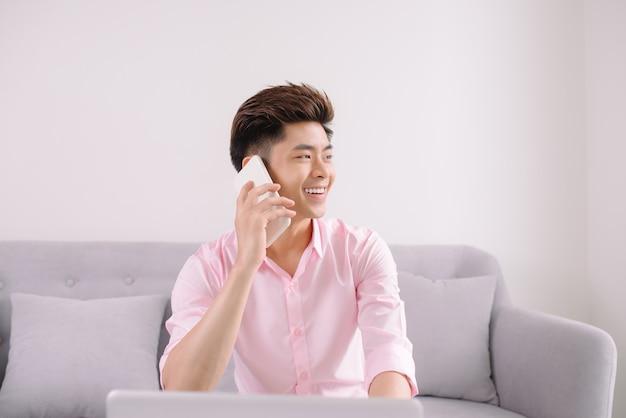 Jeune bel homme asiatique avec ordinateur portable au téléphone