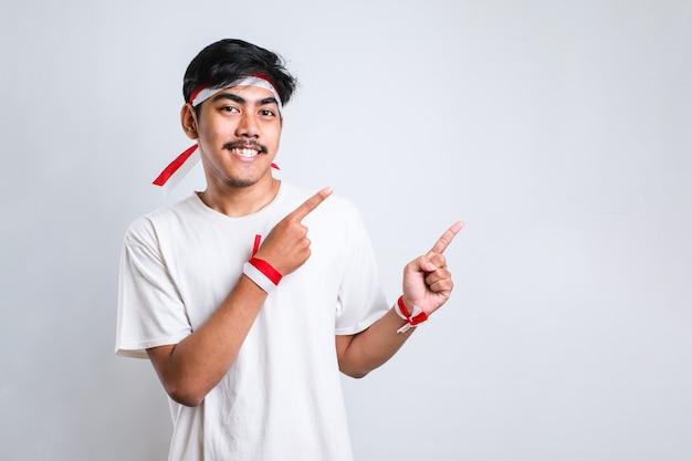 Jeune bel homme asiatique portant un bandeau rouge et blanc sur fond blanc avec un grand sourire sur le visage ; pointant avec le doigt de la main sur le côté en regardant la caméra.