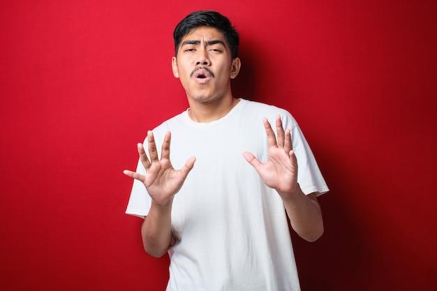 Jeune bel homme asiatique portant une chemise décontractée debout sur fond rouge s'éloignant les paumes des mains montrant le refus et le déni avec une expression effrayée et dégoûtante. arrêt et interdit.