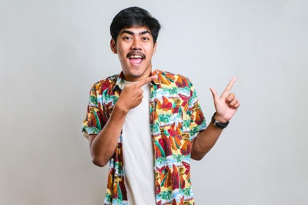 Jeune bel homme asiatique portant une chemise décontractée sur fond blanc avec un grand sourire sur le visage ; pointant avec le doigt de la main sur le côté en regardant la caméra.