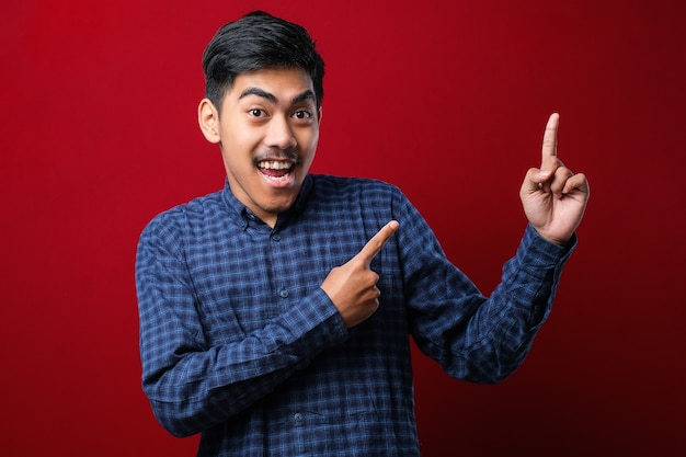 Jeune bel homme asiatique portant une chemise décontractée sur fond rouge avec un grand sourire sur le visage ; pointant avec le doigt de la main sur le côté en regardant la caméra.