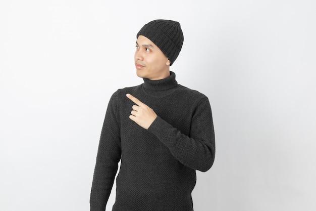 Jeune bel homme asiatique portant un pull gris et un bonnet pointant vers le côté avec les doigts pour présenter un produit ou une idée