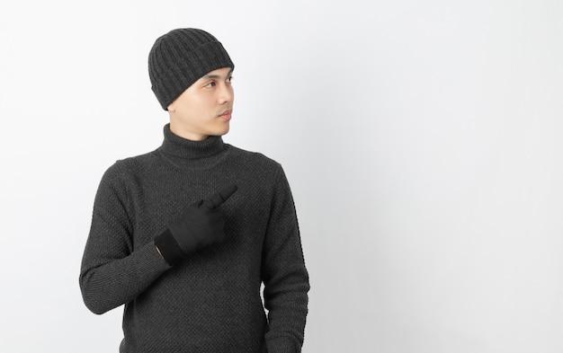 Jeune bel homme asiatique portant un pull gris, des gants et un bonnet pointant vers le côté avec les mains pour présenter un produit ou une idée sur blanc