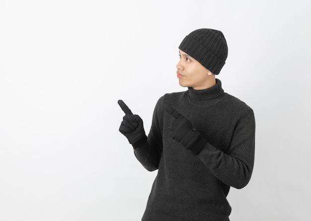 Jeune bel homme asiatique portant un pull gris, des gants et un bonnet pointant vers le côté avec les mains pour présenter un produit ou une idée