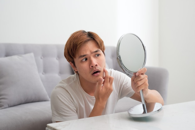 Jeune bel homme asiatique regardant son visage dans le miroir isolé