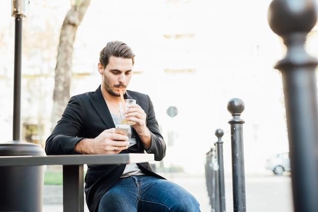 Jeune bel homme assis sur un bar dans la ville de boire un jus tout en vérifiant son téléphone intelligent