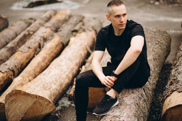 Jeune bel homme assis sur une bûche dans le parc