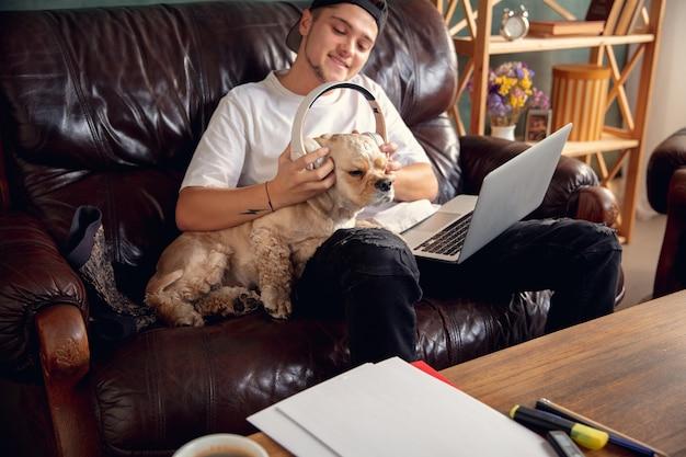 Jeune bel homme assis sur un canapé marron et travaillant avec son chien mignon