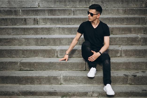 Jeune bel homme assis dans les escaliers