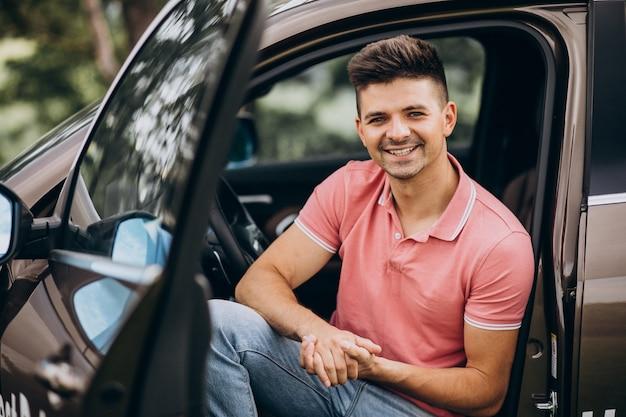 Jeune bel homme assis dans la voiture