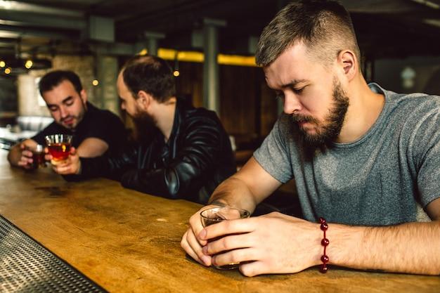 Jeune bel homme assis seul au comptoir du bar. il baisse les yeux. deux autres hommes sont derrière la conversation.