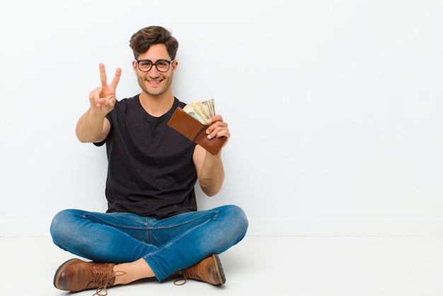 Jeune bel homme avec un et assis sur le sol assis sur le sol dans une salle blanche