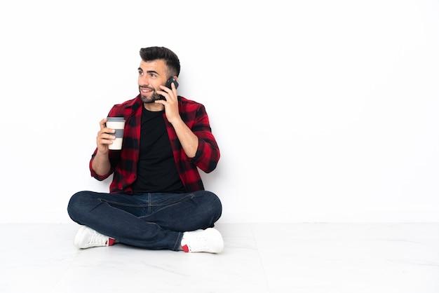 Jeune bel homme assis sur le sol tenant du café à emporter et un mobile