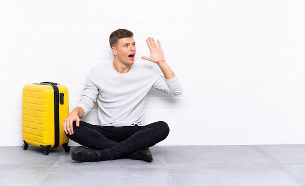 Jeune bel homme assis sur le sol avec une valise criant avec la bouche grande ouverte