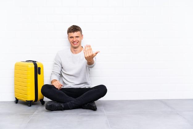 Jeune bel homme assis sur le sol avec une valise invitant à venir