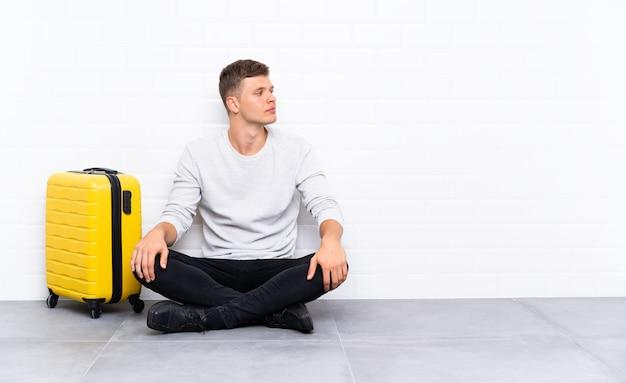 Jeune bel homme assis sur le sol avec une valise à la recherche sur le côté